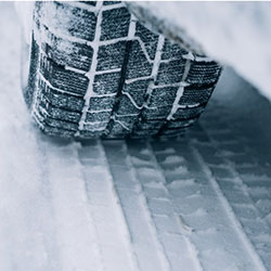 A close up of an all season tire in the snow.