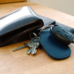 A set of car keys, house keys and a wallet on top of a desk.