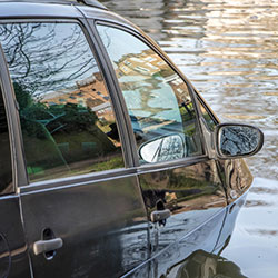 A vehicle that is stuck in flood waters with the water almost reaching its windows.