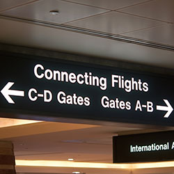 An airport sign directing travellers with connecting flights to where their gates are.
