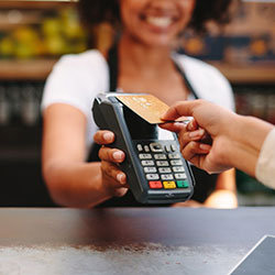 A saleswoman holding the payment machine while another woman taps it to pay for her purchase.