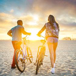 A man and woman walking their bikes on a beach at sunrise.