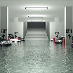 An underground garage with several cars parked. The garage is  flooded with water.