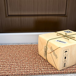 An online purchase that has been delivered and left in front of the front door on the porch.