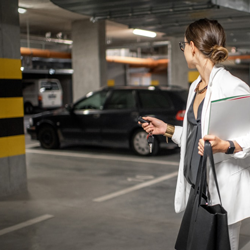 A woman in a parking garage holding her keys and locking her car using the key fob.