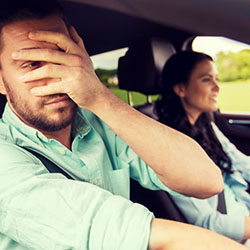A male passenger in a car covering his eyes because he's afraid of what he sees.