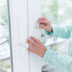 A woman setting the lock on her windows.