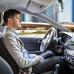 A man the wheel of a self-driving car with his hands on his lap.