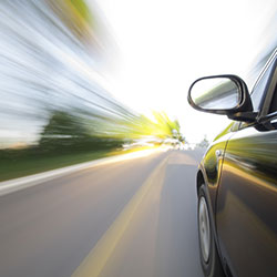 A car driving fast on a road with the scenery on the sides blurred.